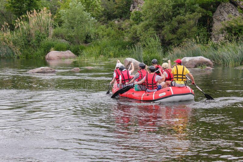 De groep mannen en vrouwen, geniet water van rafting activiteit bij rivier stock afbeeldingen