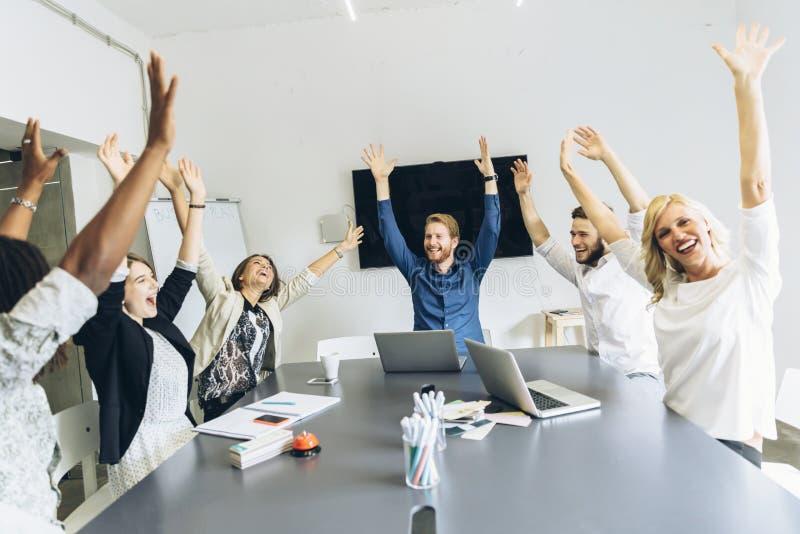 De groep medewerkers gelukkig als doel wordt bereikt stock afbeeldingen