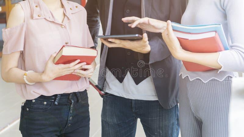 De groep mensen houdt het boek en het stationaire gebruik en de aanraking stock afbeeldingen