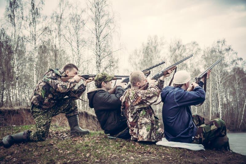 De groep mensen met kanonnen streefde aan de hemel en trof voorbereidingen om een schot te maken stock afbeelding