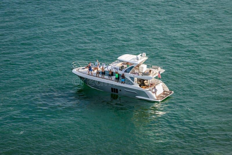 """De groep mensen op plezierboot steunt """"HAVE het teken en de golf van FUN† aan de het vertrekken Cruiseschepen royalty-vrije stock foto"""