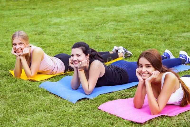 De groep mooie tevreden gezonde slijmerige jonge vrienden heeft rust na het doen van exersices op het groene gras in park, ligt o stock afbeeldingen