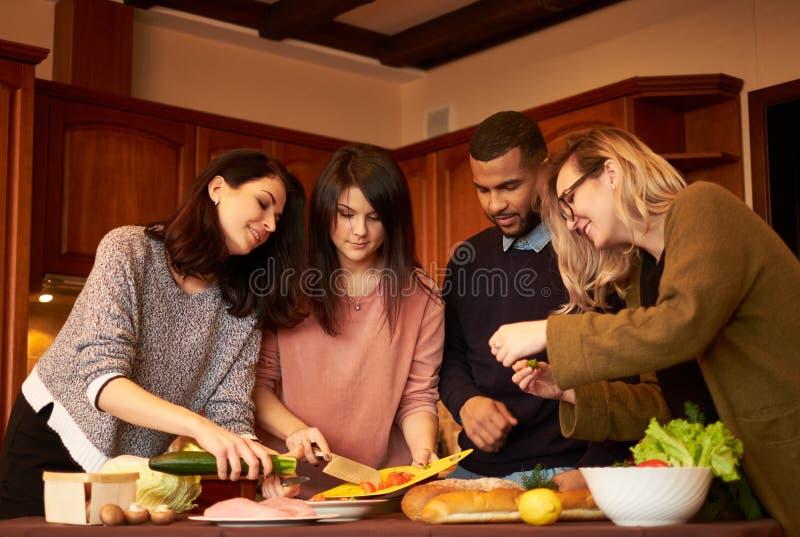 De groep multi etnische jonge vrienden in keuken treft voor partij voorbereidingen royalty-vrije stock foto's