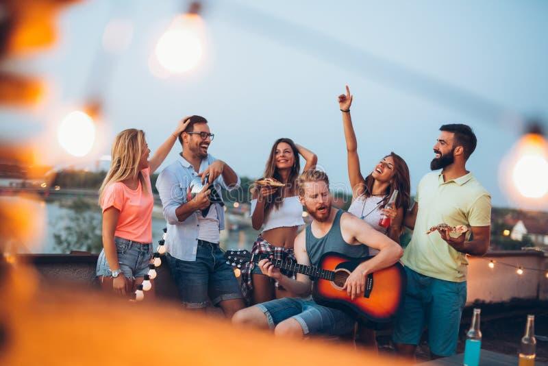 De groep onbezorgde vrienden die heeft pret in de zomer dansen stock afbeelding