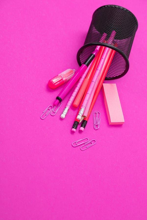 De groep de roze producten van de kleurenkantoorbehoeften is van boven tot onder verspreid van potloodbak op roze geïsoleerde ach stock foto's