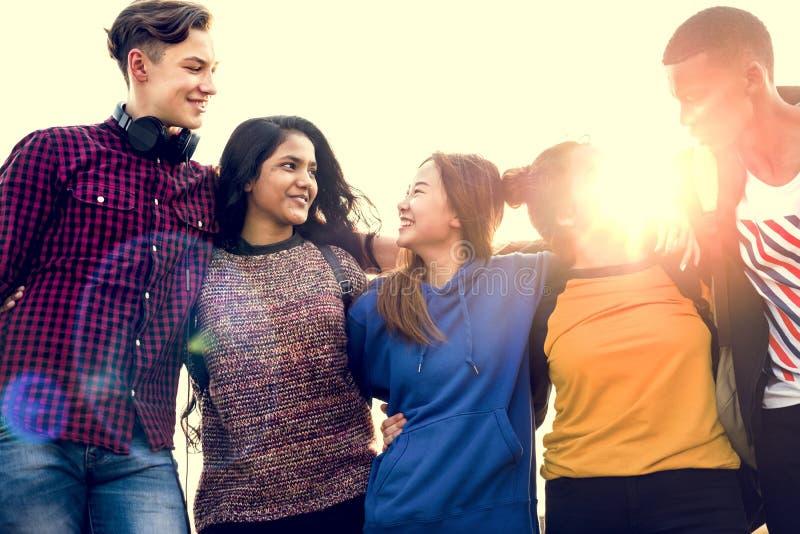 De groep schoolvrienden bewapent in openlucht rond elkaar samenhorigheid en communautair concept royalty-vrije stock afbeeldingen