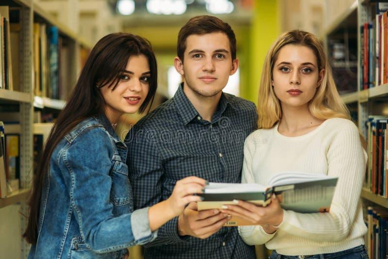 De groep student wil wat nuttige literatuur aan het voorbereidingen treffen voor universitair examen vinden royalty-vrije stock foto