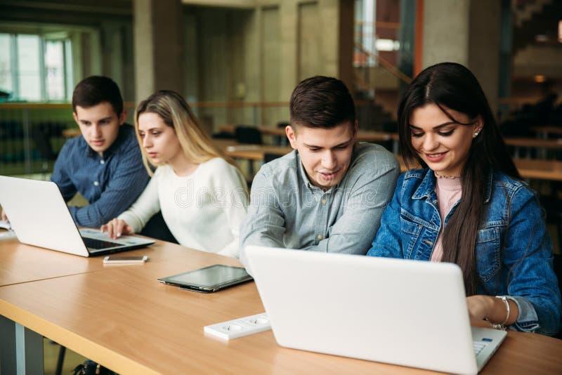 De groep studenten die in de schoolbibliotheek bestuderen, een meisje en een jongen gebruiken laptop en verbinden met Internet stock foto