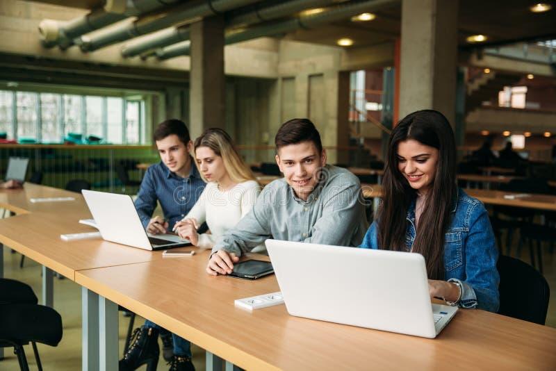 De groep studenten die in de schoolbibliotheek bestuderen, een meisje en een jongen gebruiken laptop en verbinden met Internet stock foto's