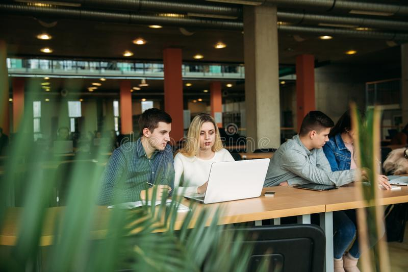 De groep studenten die in de schoolbibliotheek bestuderen, een meisje en een jongen gebruiken laptop en verbinden met Internet stock fotografie