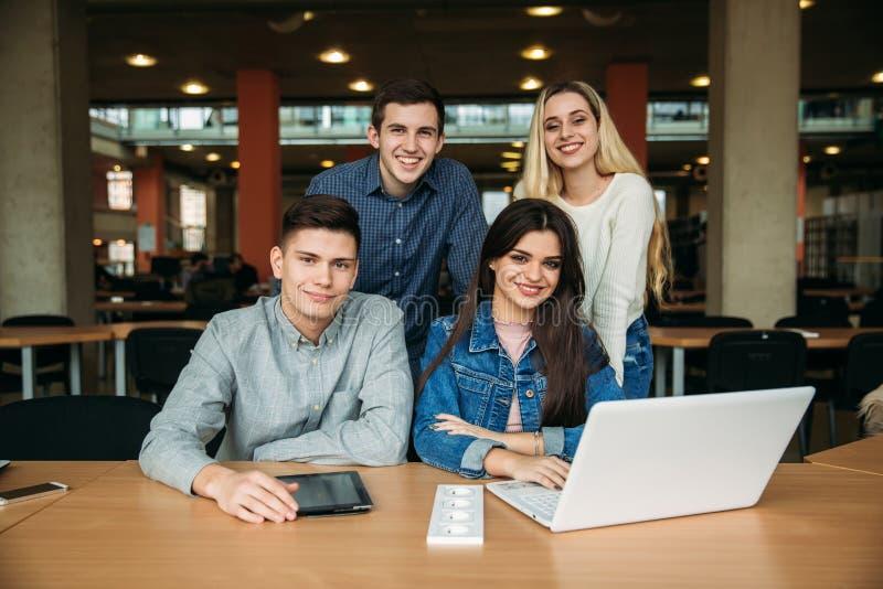 De groep studenten die in de schoolbibliotheek bestuderen, een meisje en een jongen gebruiken laptop en verbinden met Internet royalty-vrije stock foto