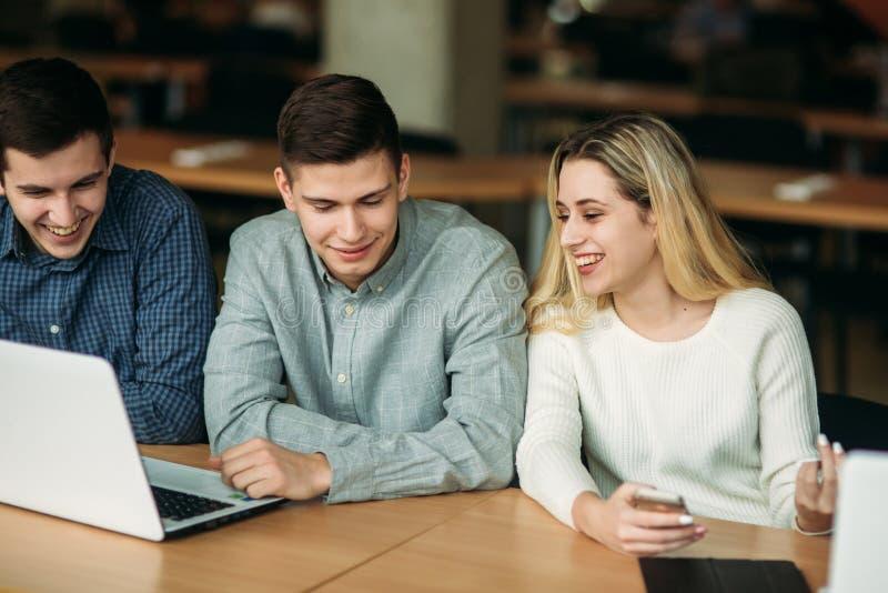 De groep studenten die in de schoolbibliotheek bestuderen, een meisje en een jongen gebruiken laptop en verbinden met Internet stock afbeelding