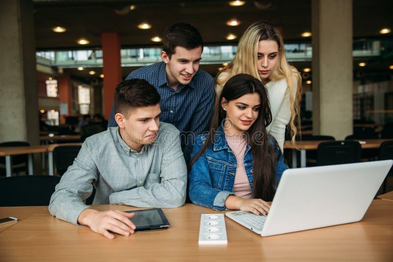 De groep studenten die in de schoolbibliotheek bestuderen, een meisje en een jongen gebruiken laptop en verbinden met Internet royalty-vrije stock afbeelding