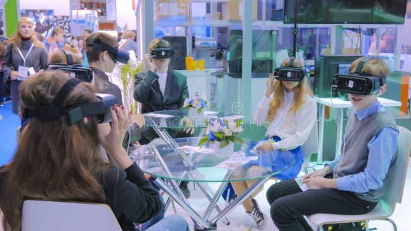 De groep tieners die virtuele werkelijkheidshoofdtelefoon met behulp van bij technologie toont stock afbeelding