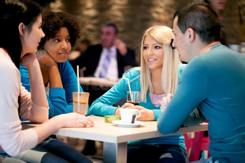De groep tieners in een koffie geniet van stock foto