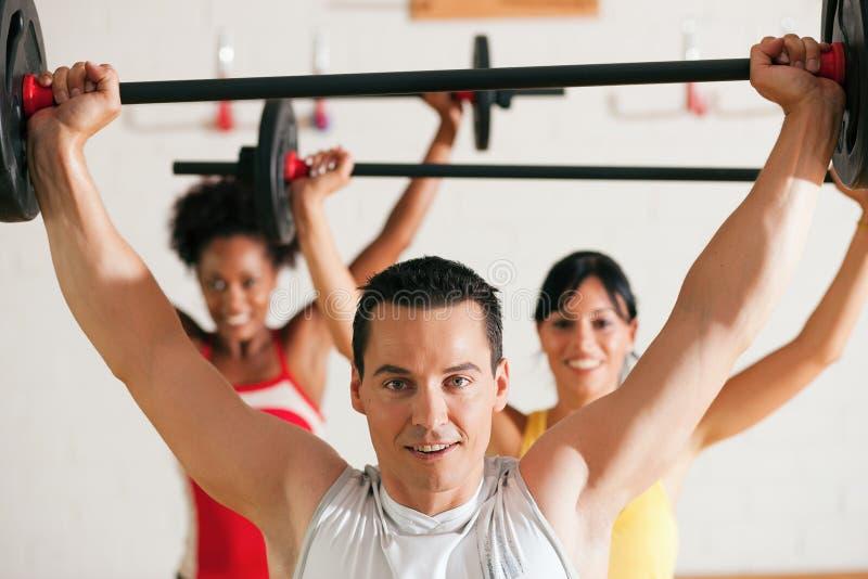 De groep van de geschiktheid met barbell in gymnastiek stock fotografie
