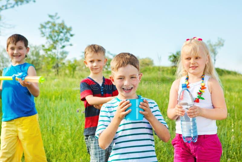 De groep van jonge geitjes met stuk speelgoed waterkanonnen stock foto's