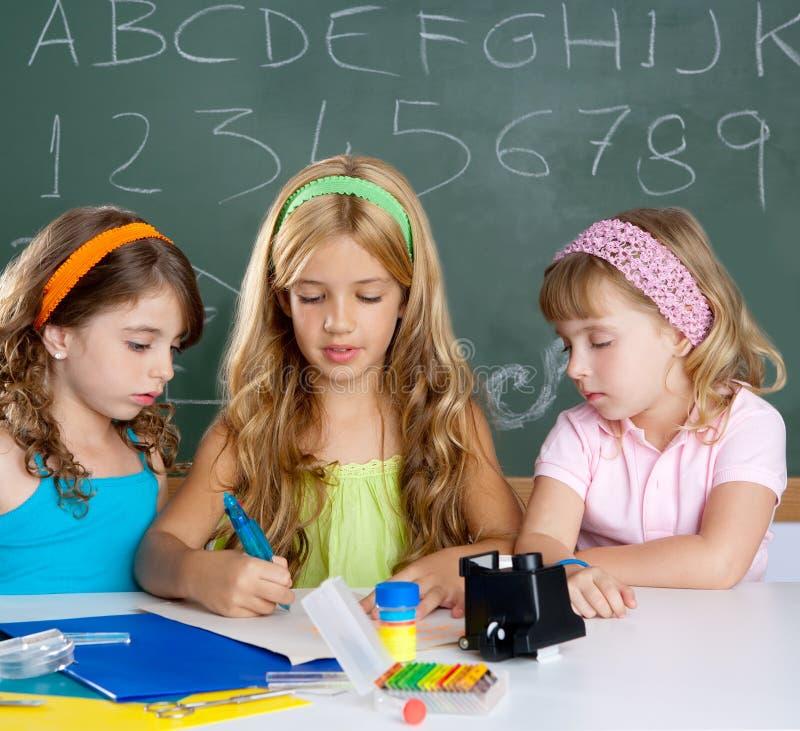 De groep van jonge geitjes studentenmeisjes bij schoolklaslokaal stock afbeeldingen