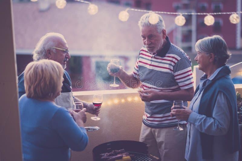 De Groep van Nice Kaukasische volwassen mensen in geluk die samen openlucht voor diner blijven in het terras Liefde en vriendscha stock afbeelding
