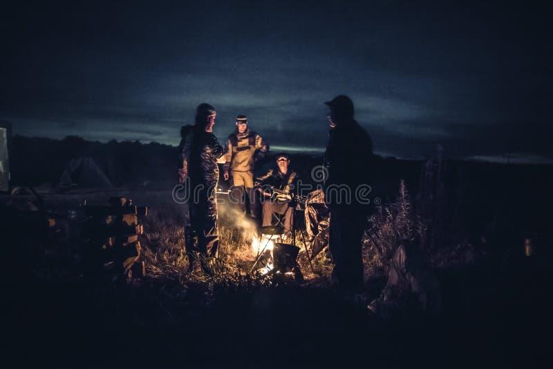 De groep van de de reizigerstoerist van mensenmensen rustende het kampbrand in in openlucht kampeert na lange de jachtdag in de n stock foto