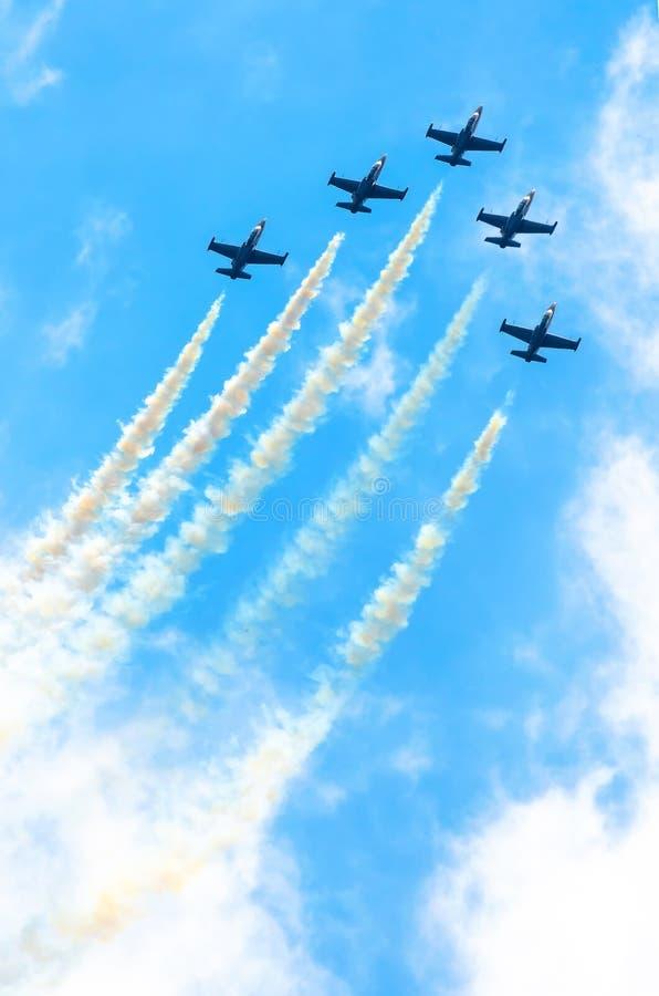 De groep vechtersvliegtuigen vliegt omhoog met een rookspoor tegen een blauwe hemel met wolken royalty-vrije stock afbeelding