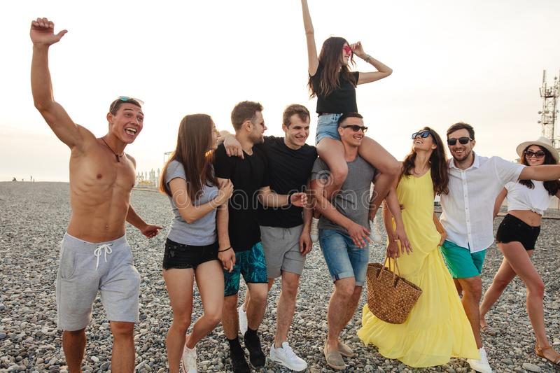 De groep Vrienden die bij Strand lopen, die pret, het vervoer per kangoeroewagen van de vrouw hebben bemant, grappige vakantie royalty-vrije stock foto's