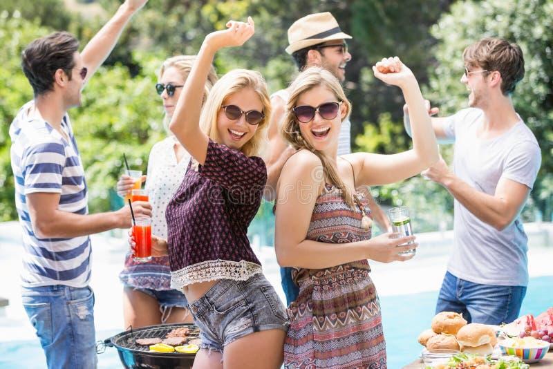 De groep vrienden die dansen bij in openlucht roostert partij stock fotografie