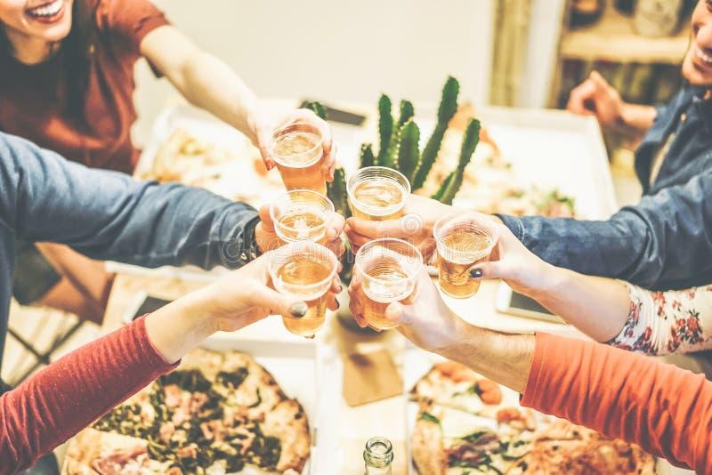De groep vrienden die diner van het roosteren met bieren en het eten genieten haalt thuis pizza weg - Toejuichingen van gelukkige stock foto's