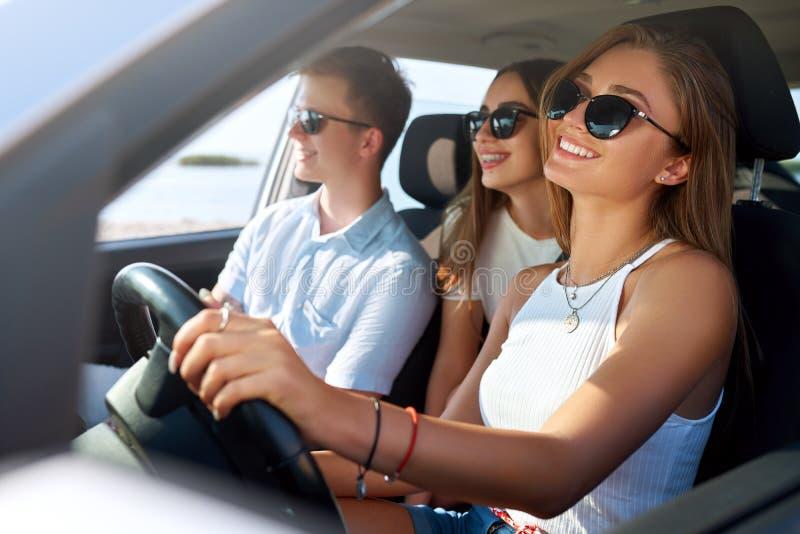 De groep vrienden huurde een auto op de reis van de de zomerweg en kwam aan het overzeese strand aan Meisje die pret met vrienden stock foto