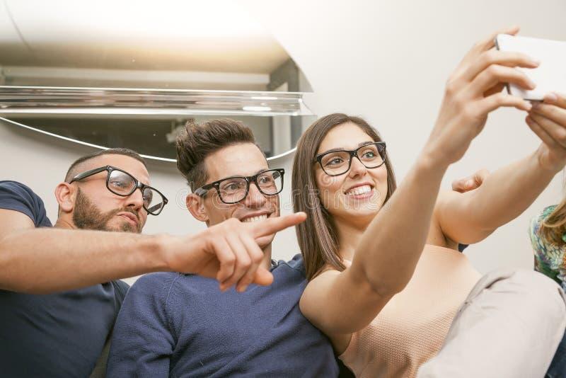 De groep vrienden op laag neemt een selfie op een grappige manier royalty-vrije stock fotografie
