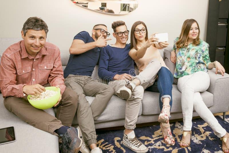De groep vrienden op laag neemt een selfie op een grappige manier royalty-vrije stock afbeeldingen