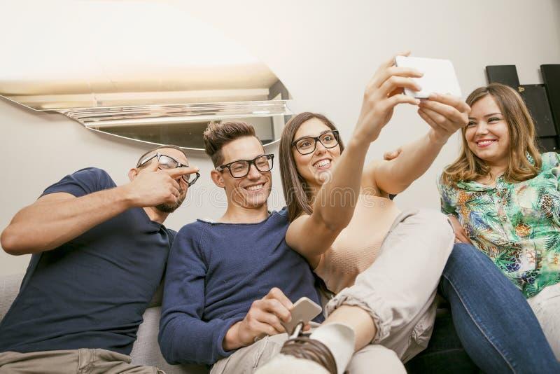 De groep vrienden op laag neemt een selfie op een grappige manier royalty-vrije stock foto