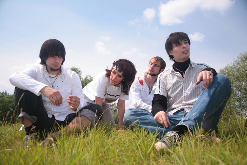 De groep vrienden zit op gras royalty-vrije stock foto