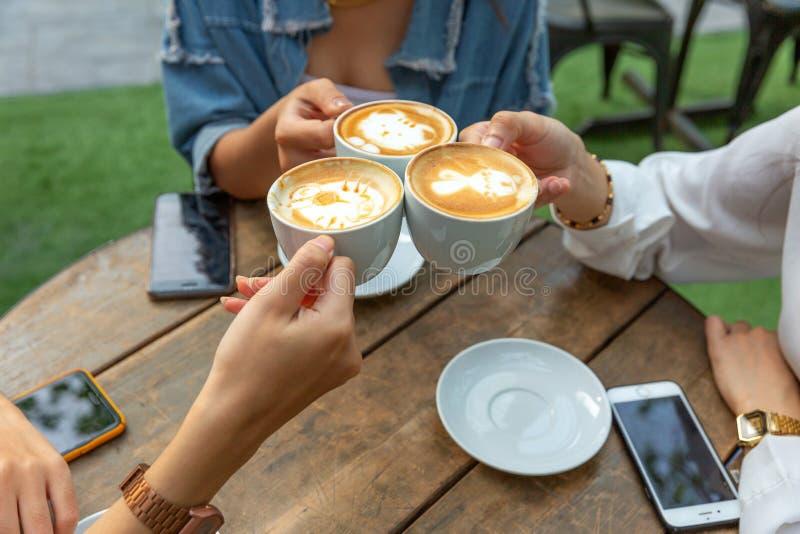De groep vriendentoejuichingen met latae vormt in koffiebar tot een kom met telefoon op lijstzitting openlucht bij koffie - Jonge stock afbeelding