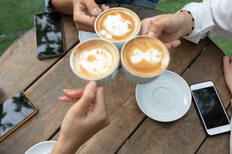 De groep vriendentoejuichingen met latae vormt in koffiebar tot een kom met telefoon op lijstzitting openlucht bij koffie - Jonge royalty-vrije stock fotografie