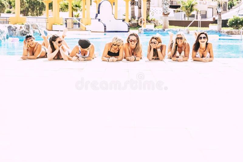 De groep vrolijke gelukkige mensen bepaalt bij de pool op een witte vloer - vriendschap en jonge vrouwen op vakantieconcept - vri royalty-vrije stock afbeeldingen