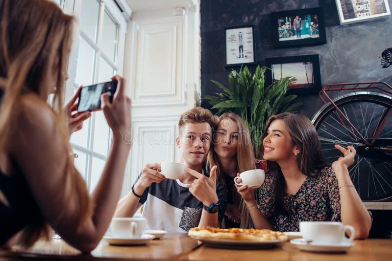 De groep vrolijke jongeren die in een koffie het drinken koffie het maken stellen ziet terwijl hun vriend die hen fotograferen me stock afbeelding