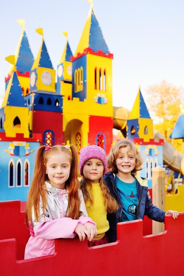 De groep vrolijke kinderen speelt in het Pretpark op de achtergrond van een kleurrijk sprookjekasteel stock afbeelding