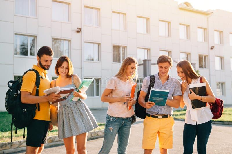 De groep vrolijke studententieners met notaboeken bestudeert in openlucht bij campus Onderwijs en tienerconcept stock afbeelding