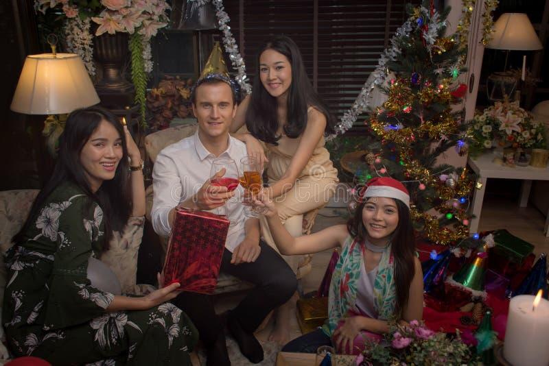 De groep vrolijke vrienden viert Kerstmis en het Nieuwjaar geeft samen een toost royalty-vrije stock afbeelding