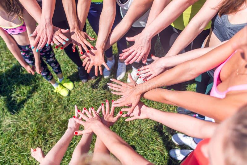De groep vrouwen die hun schoonheid zetten overhandigt samen de modieuze kleurrijke manicure van de spijkerskunst stock afbeelding