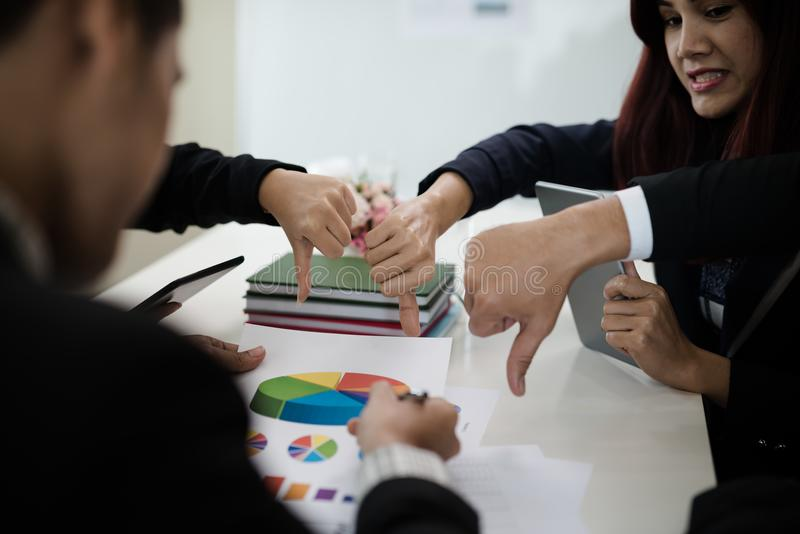 De groepen Aziatische zakenlieden tonen afkeer of in tegenstelling tot duimen onderaan h royalty-vrije stock afbeelding