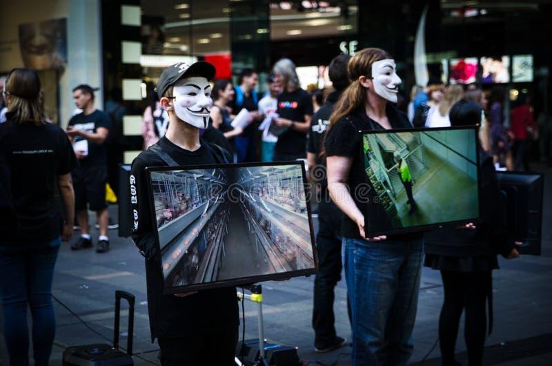 De groepen mensen zetten op het anonieme masker en houden de het schermmonitor om informatie over wreedheid van dierlijke landbou stock afbeelding