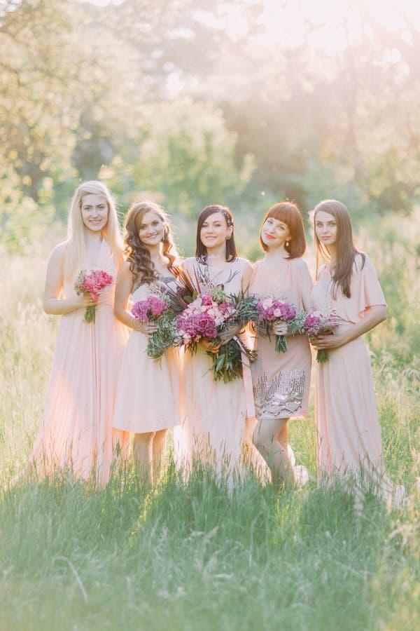 De groepsfoto van de bruid en de bruidsmeisjes die de reusachtige roze boeketten in het midden van het zonnige groene bos houden stock fotografie