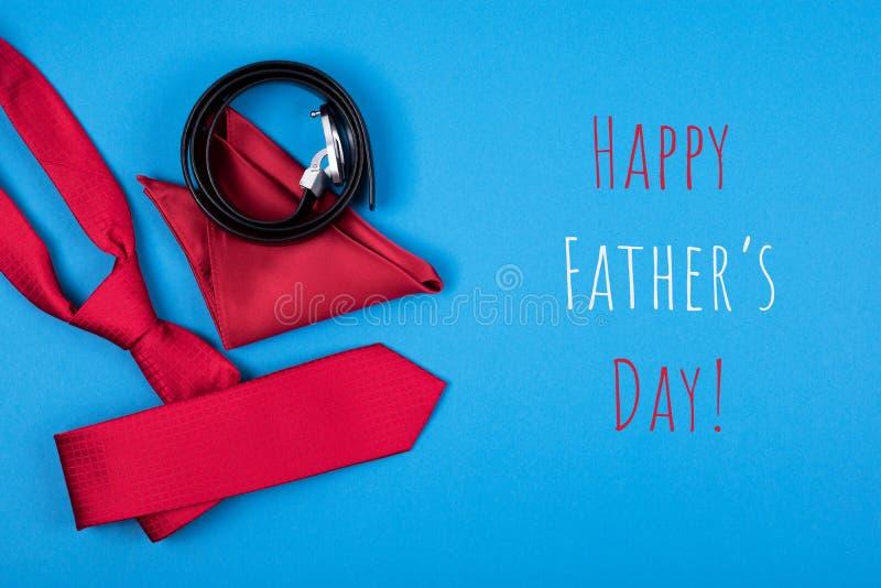 De groetkaart met samenstelling van rode halsband, in eigen zak steekt vierkant en riem op blauwe achtergrond met inschrijvings G stock afbeeldingen
