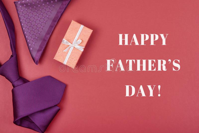 De groetkaart met samenstelling van violette halsband, giftdoos, in eigen zak steekt vierkant met inschrijvings Gelukkige Vaderda stock foto's