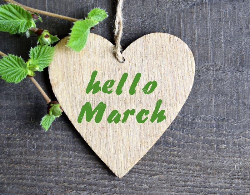 De de groetkaart van Hello Maart met decoratief hart en de groene de lenteboom vertakken zich op oude houten achtergrond De lente stock fotografie