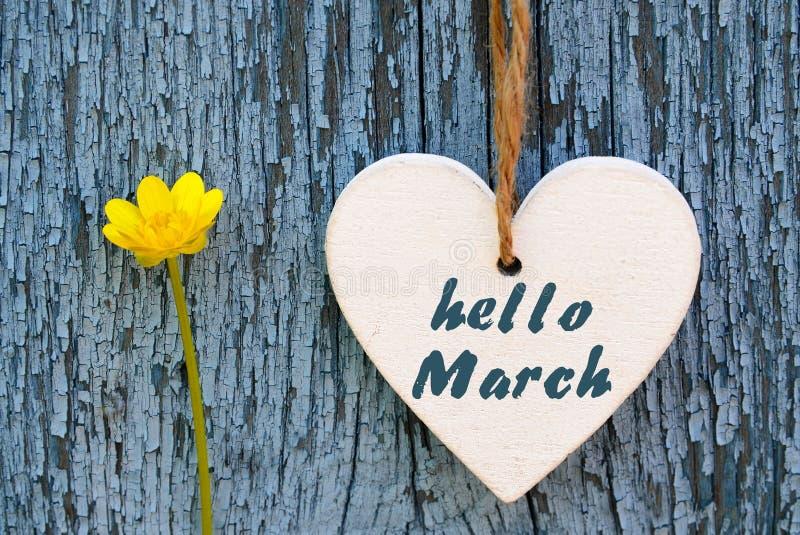 De de groetkaart van Hello Maart met decoratief wit hart en de gele lente bloeien op oude blauwe houten achtergrond royalty-vrije stock foto's
