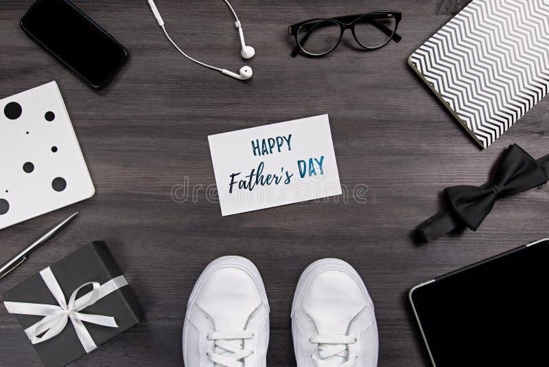 De groetkaart van de vadersdag met mensentoebehoren, witte toevallige tennisschoenen, gadgets op donkere houten achtergrond royalty-vrije stock foto