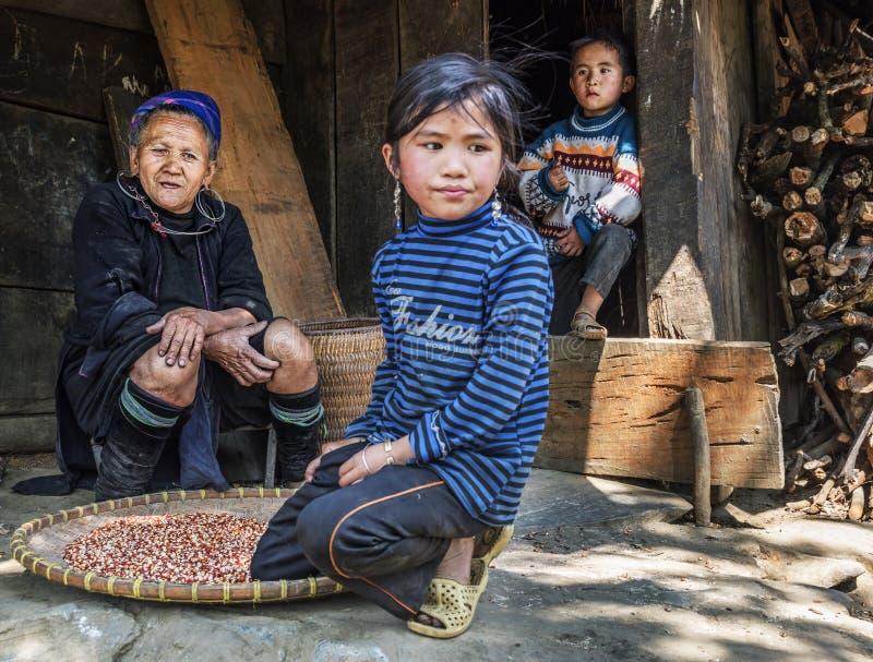 De grootmoeder die van de Hmongstam buiten haar huis met haar twee kleinkinderen in een klein dorp, Sapa, Vietnam rusten stock afbeeldingen